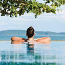 die Rückseite einer Frau, die sich in einem wahrscheinlichen Pool bei schönem Wetter entspannt